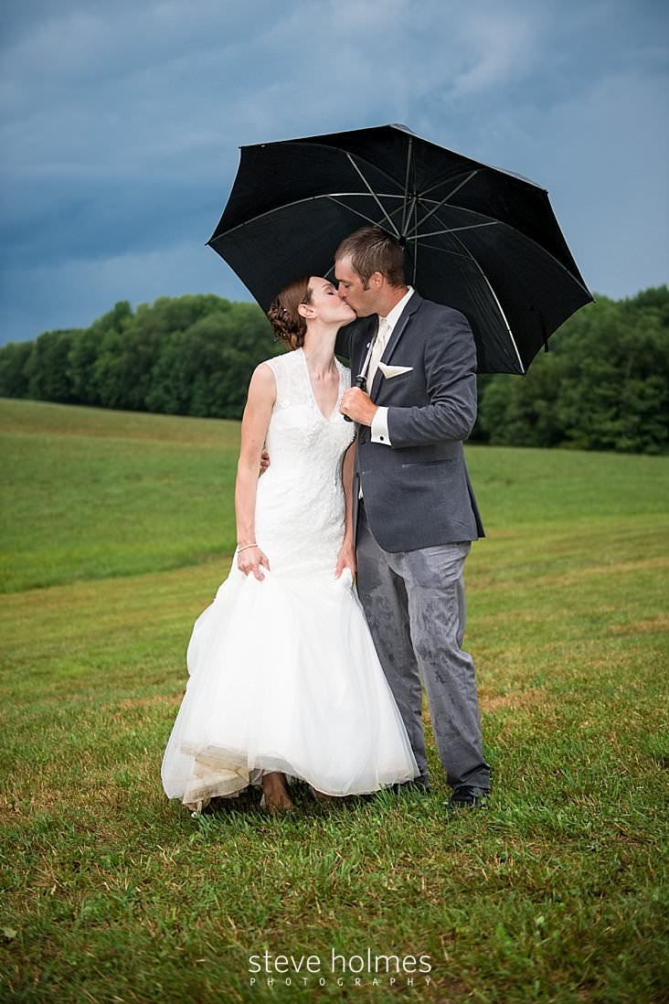 54_Bride and groom kiss under an umbrella and stormy skies.jpg