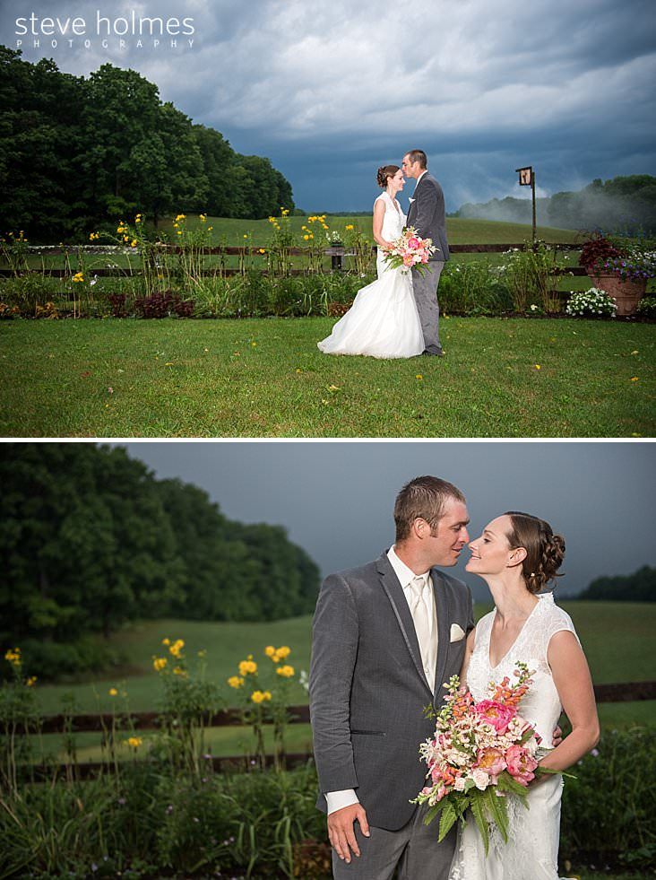 55_Groom kisses bride on forehead in front of gardens with stormy skies and mist rising in background.jpg