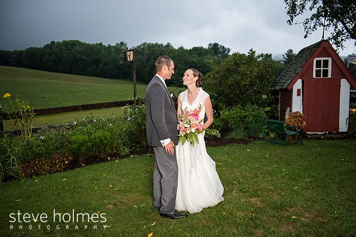 59_Bride smiles at groom in front of garden and shed.jpg
