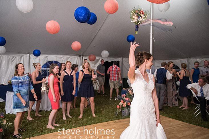 66_Bride tosses bouquet to ladies under tent.jpg
