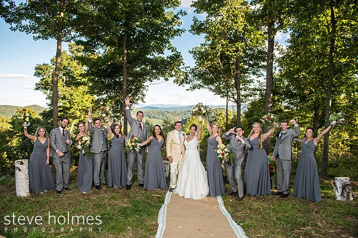 Bridal party throw their hands in the air with Green mountains in background.jpg