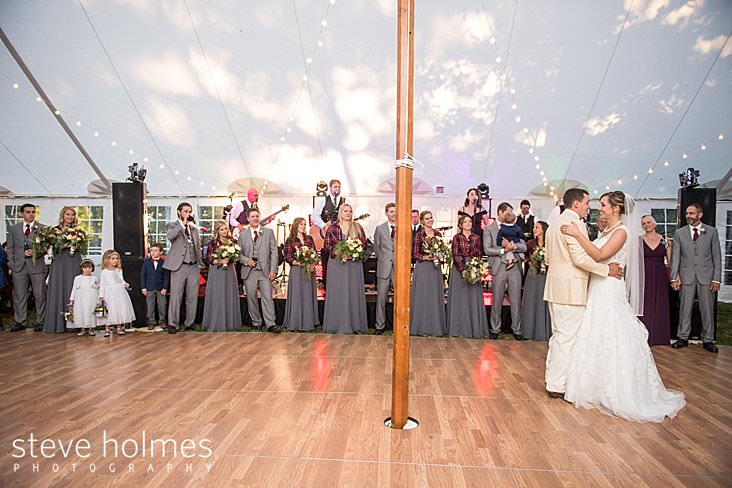 Bridal party watches as bride and groom dance their first dance under tent.jpg