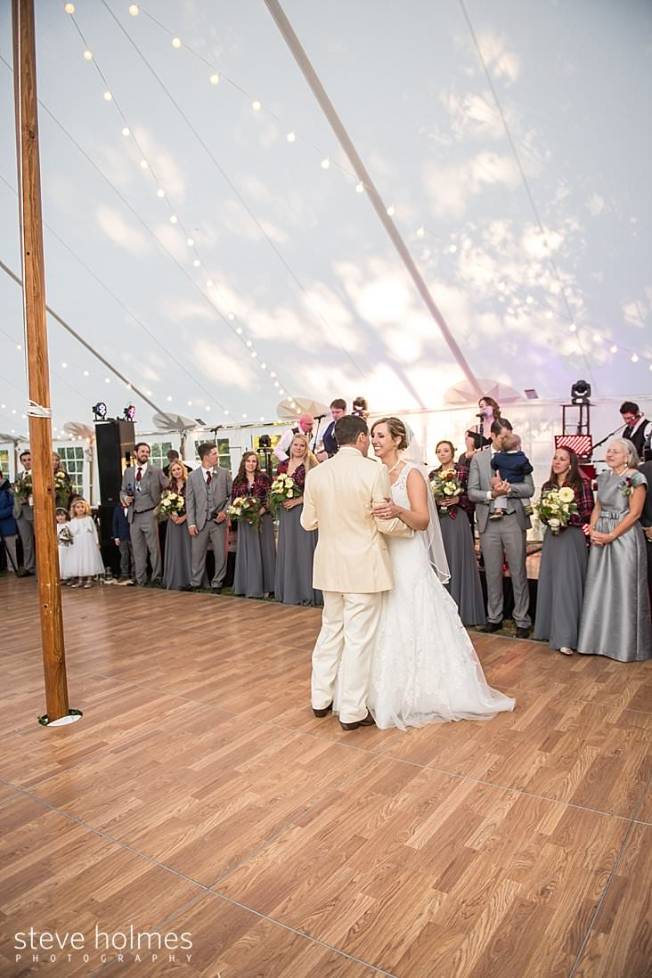 Bride and groom have first dance under white tent.jpg