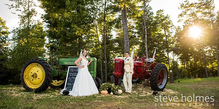 Bride and groom pose in front of their family tractors.jpg