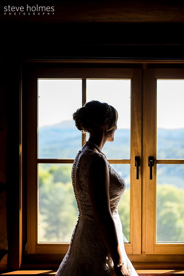 Bride looks out of window at mountains.jpg