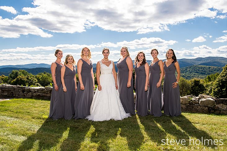 Bride poses in front of stone wall with bridesmaids and Vermont mountains in background.jpg