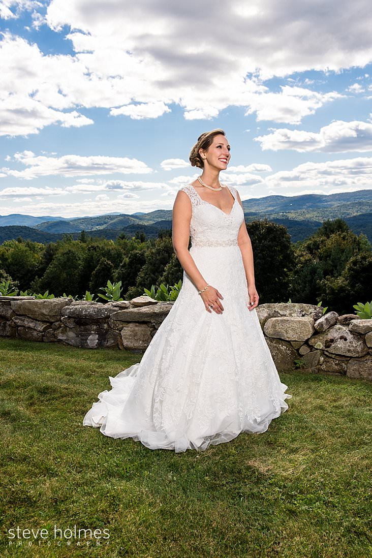 Bride stands before a stone wall and Vermont Green mountains in background.jpg