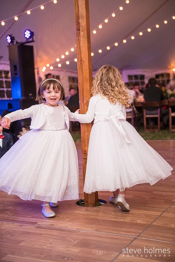 Flower girls swing each other on dance floor.jpg