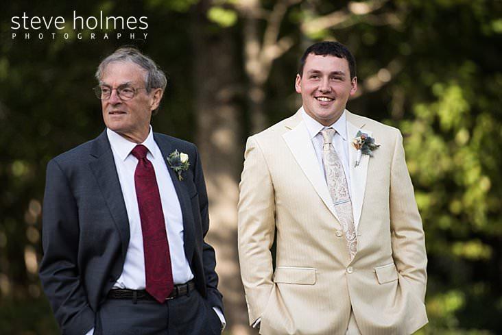 Groom waits casually in white tuxedo.jpg