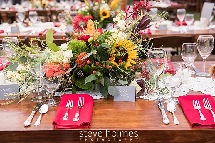 Table setting for wedding reception with woods tables, red napkins and sunflowers.jpg