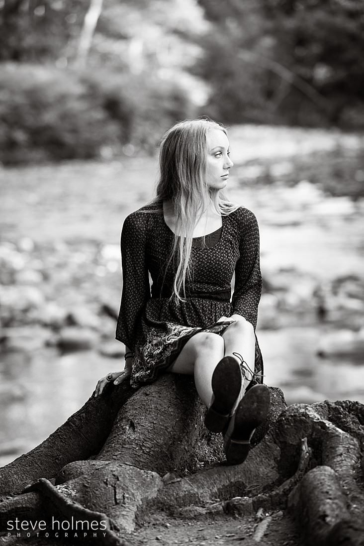 06_Teen sits on stump by river wearing long sleeve babydoll dress in black and white portrait.jpg