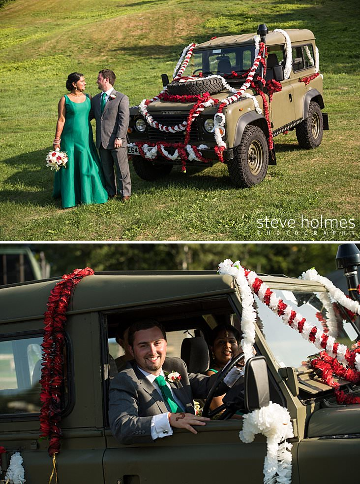 104_Bride and groom smile at each other next to land rover decorated in white and red flower chains.jpg
