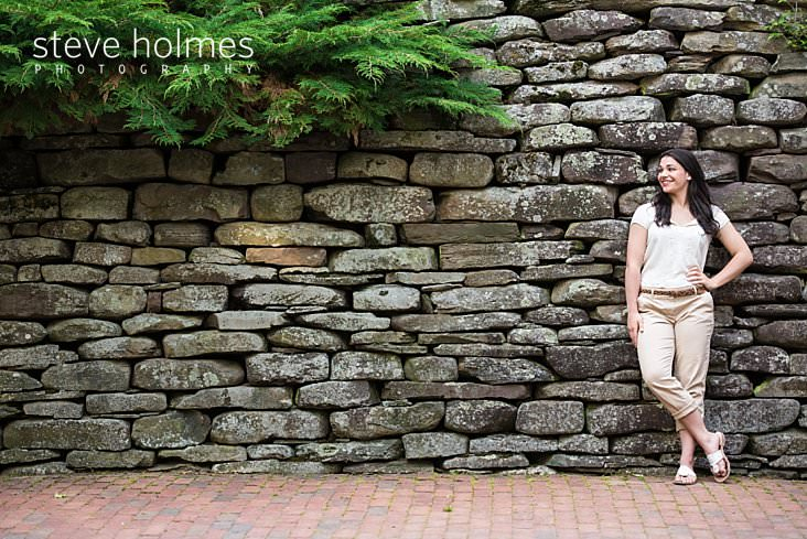 13_Brunette girl looks to the side while posing in front of a stone foundation.jpg