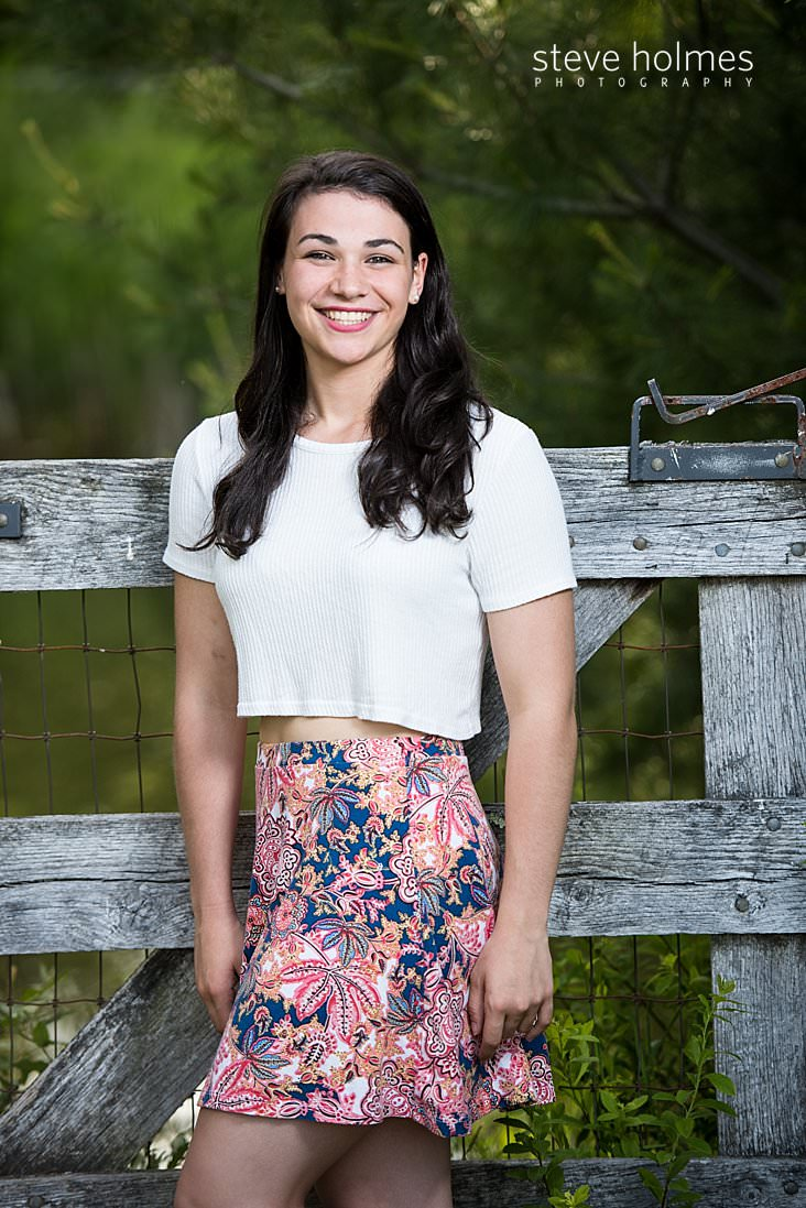 14_Teen girl stands in front of wooden fence wearing white tee shirt and flowered skirt.jpg