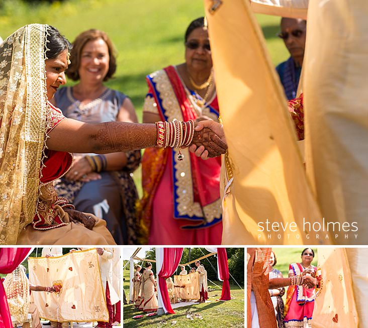 65_Groom reaches through tapestry to hold bride's hand.jpg