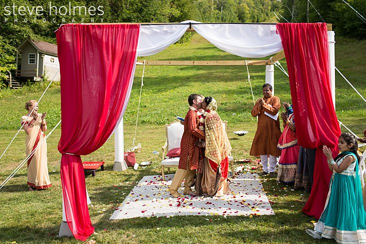 91_Bride and groom kiss at altar surrounded by flower petals.jpg