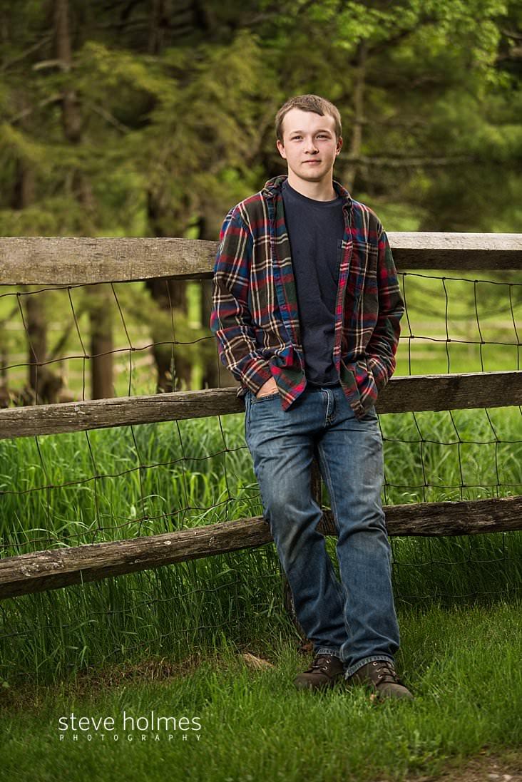 07_teen boy leans against fence in outdoor portrait.jpg