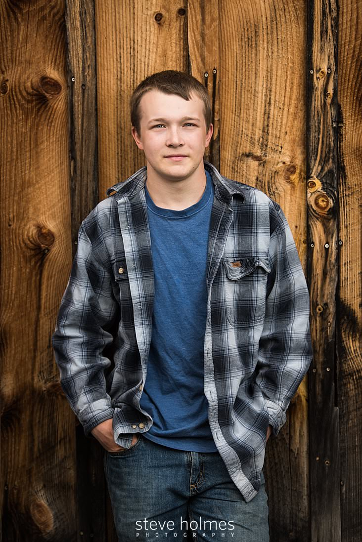 12_teen in flannel jacket stands before weathered wooden siding.jpg