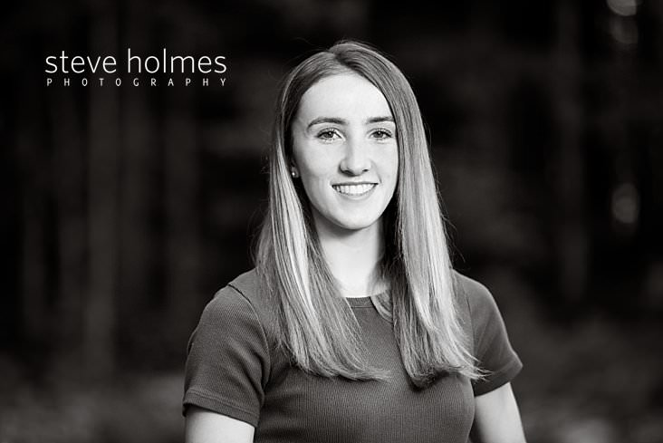 16_Young woman smiles in black and white senior portrait.jpg