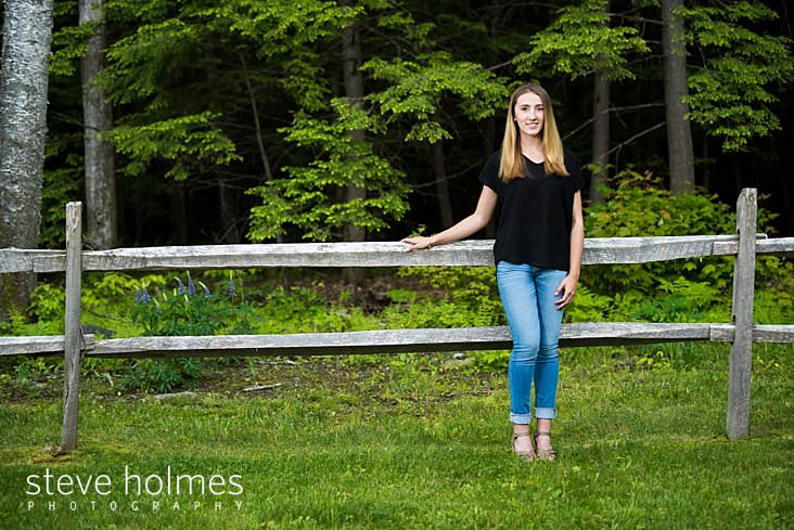 20_Young girl wearing jeans and a black shirt leans against fence in outdoor portrait.jpg