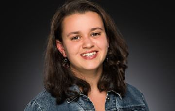 Girl wearing jean jacket smiles in studio portrait