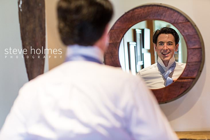 02_Groom ties his tie in the reflection of a round mirror.jpg