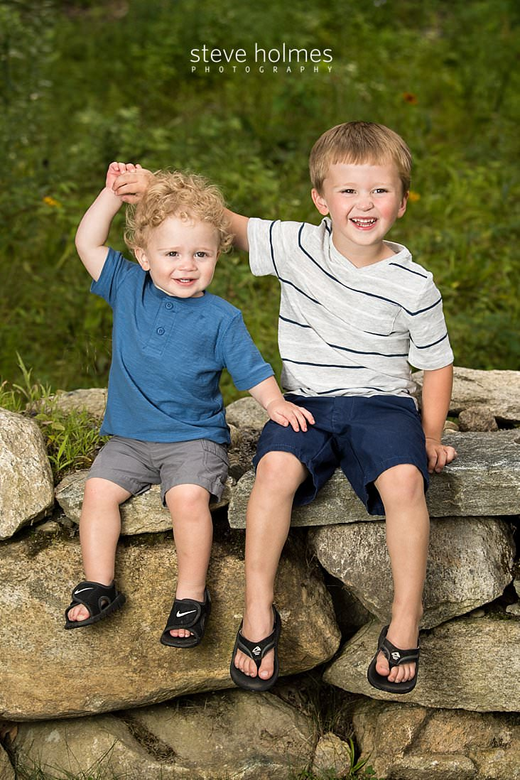 03_Brothers hold hands and sit on a stone wall.jpg