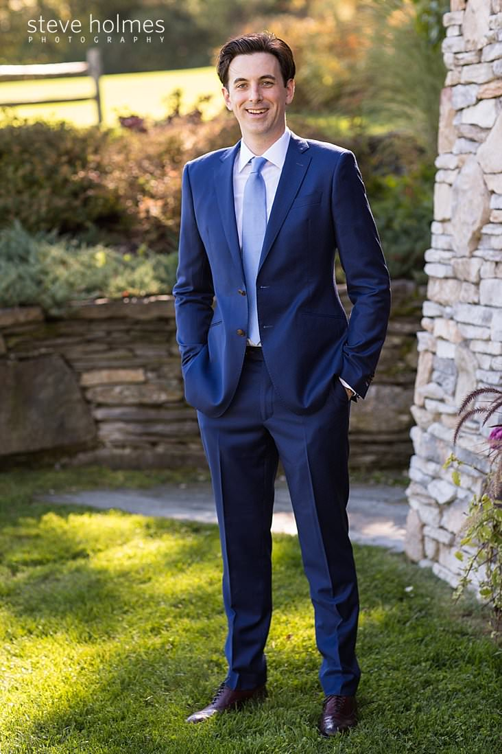 07_Groom in blue suit stands outside with his hands in his pockets.jpg