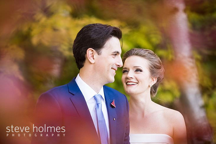 24_Bride and groom smile at each other outside framed by leaves.jpg
