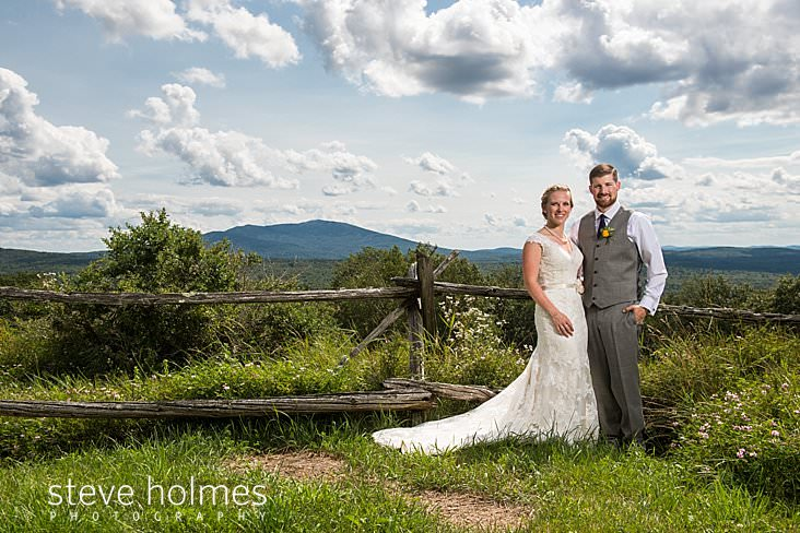 24_Bride and groom stand in front of old wooden fence with Green Mountain range behind them.jpg