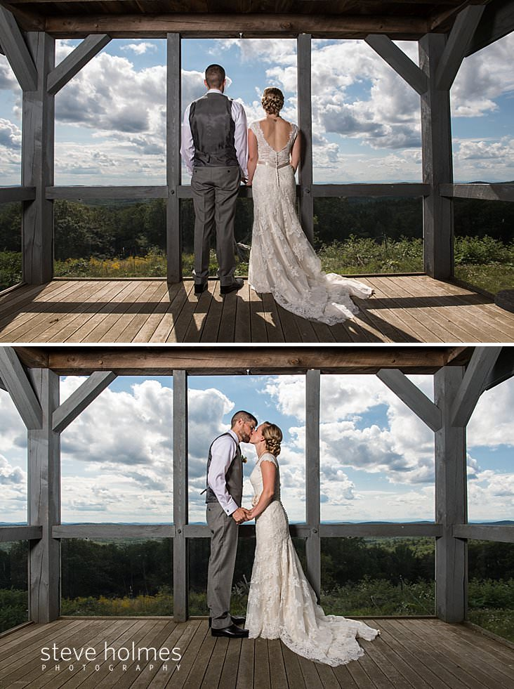 25_Bride and groom look out from screened-in cabin overlooking Green Mountain range.jpg