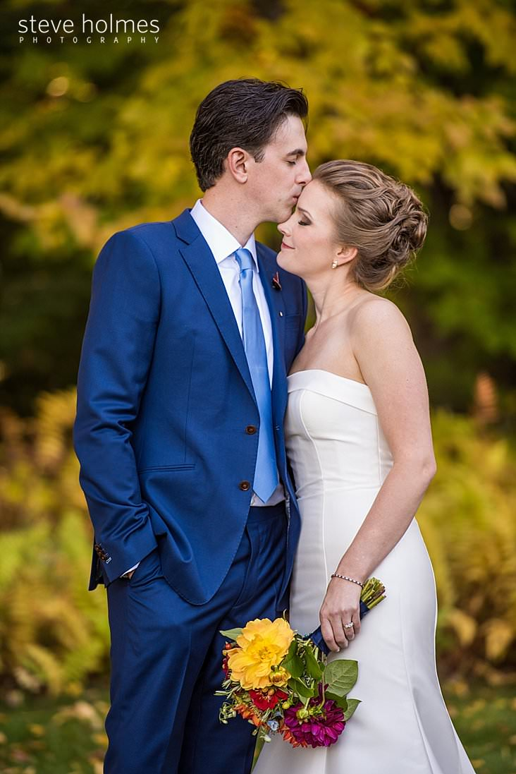 25_Groom kisses bride on forehead outside on autumn day.jpg