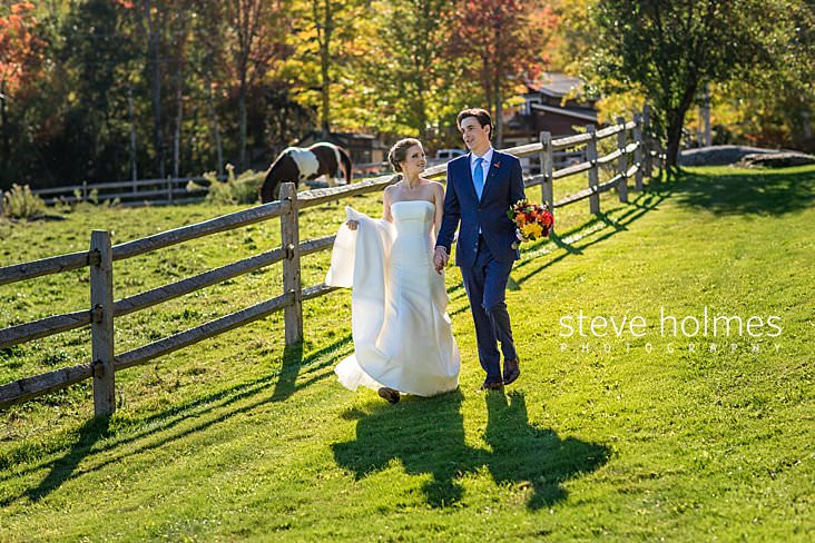 28_Bride and groom walk together along fence with horse in background.jpg