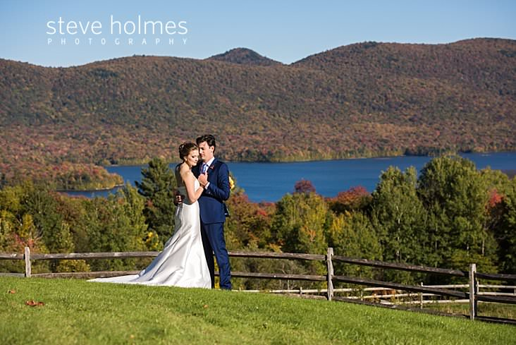 29_Bride and groom hold each other on a hillside overlooking a lake and mountains.jpg