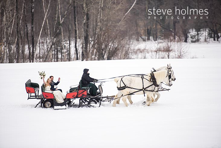 34_Bride and groom wave as they are pulled in sleigh by two white horses.jpg