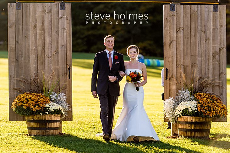 36_Bride walks with father through sliding barn doors down isle.jpg