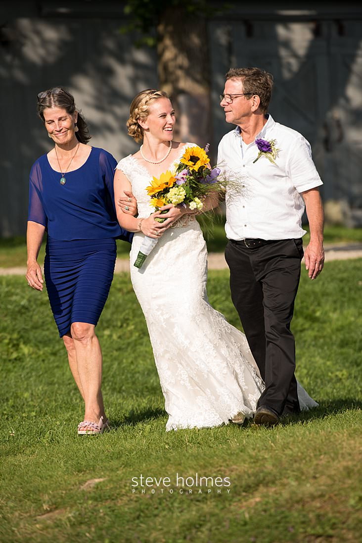 42_Bride walks with her parents to outdoor ceremony.jpg
