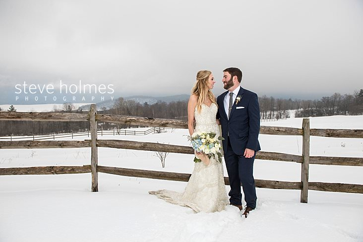 43_Bride and groom look at each other in front of fence and snowy landscape.jpg