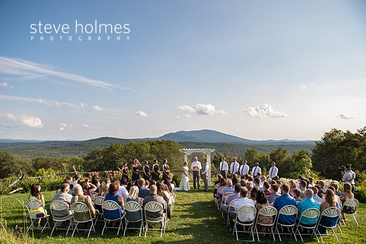 45_Wedding ceremony in Vermont takes place outside overlooking mountain range.jpg
