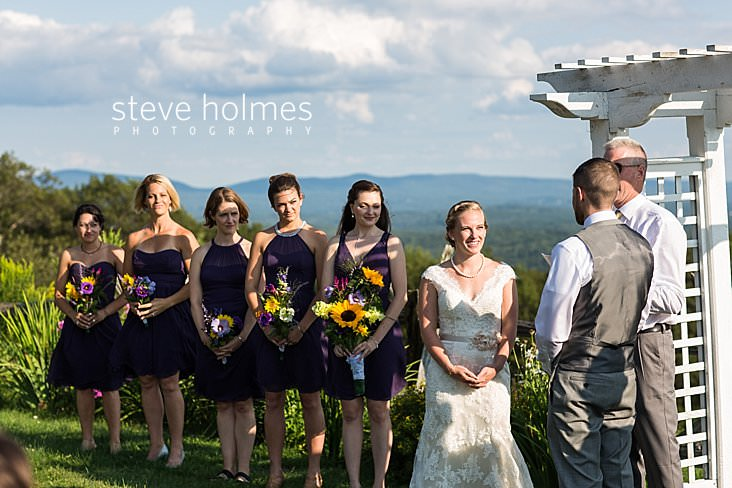 46_Bride stands with bridesmaids flanking her in outdoor ceremony_.jpg