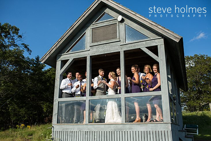 53_Bridal party enjoys a celebratory shot on porch of cabin.jpg