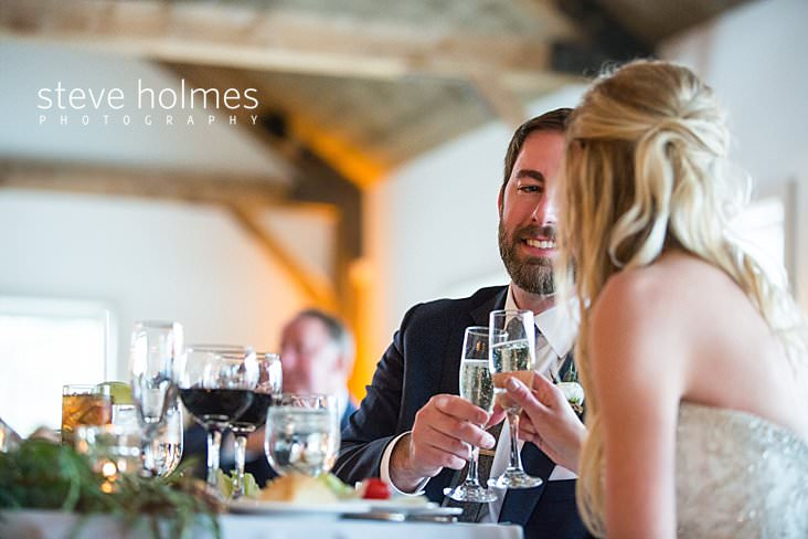56_Bride and groom toast each other at their rustic, sweetheart table.jpg