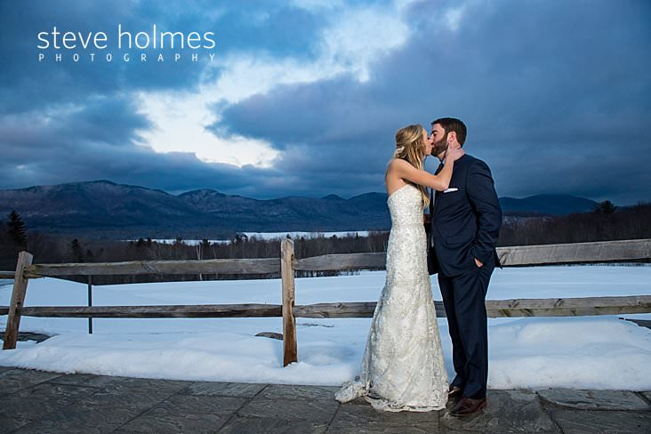 62_Bride and groom kiss outside on patio overlooking winter mountain sunset.jpg