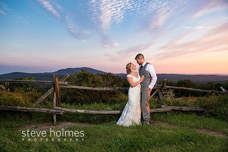 62_Bride and groom smile at each other along fence at sunset.jpg