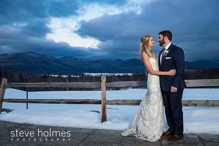 63_Bride and groom smile at each other on patio overlooking winter mountain landscape.jpg