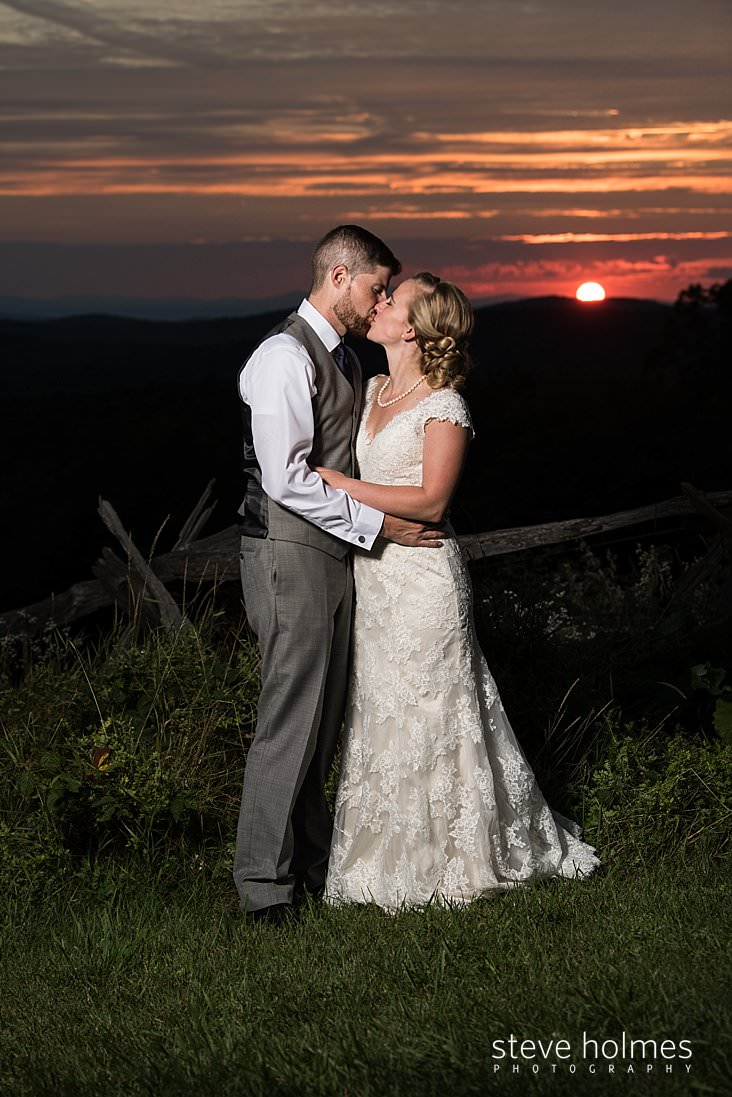 66_Bride and groom kiss at sunset.jpg