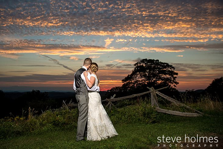 67_Bride and groom hold each other at sunset on mountain ridge.jpg