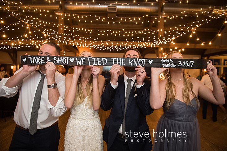 70_Bride and groom take a shot off of a ski with bridal party.jpg