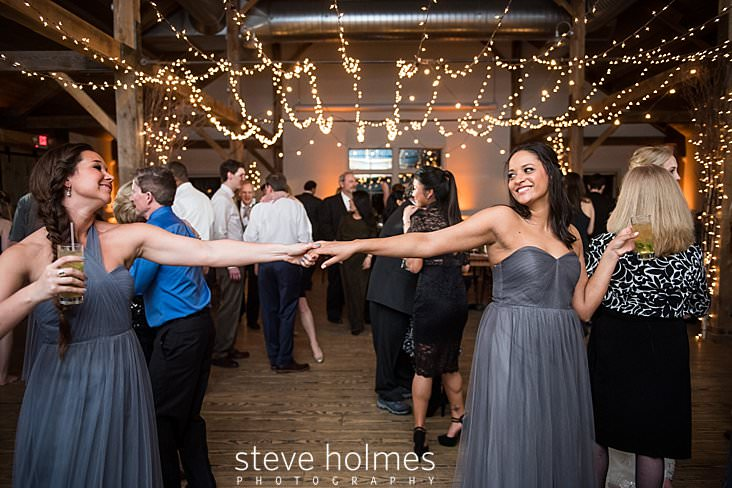74_Bridesmaids in grey maxi dresses dance together under stringed lights.jpg