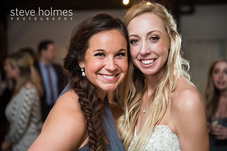 75_Blonde bride and bridesmaid smile together.jpg